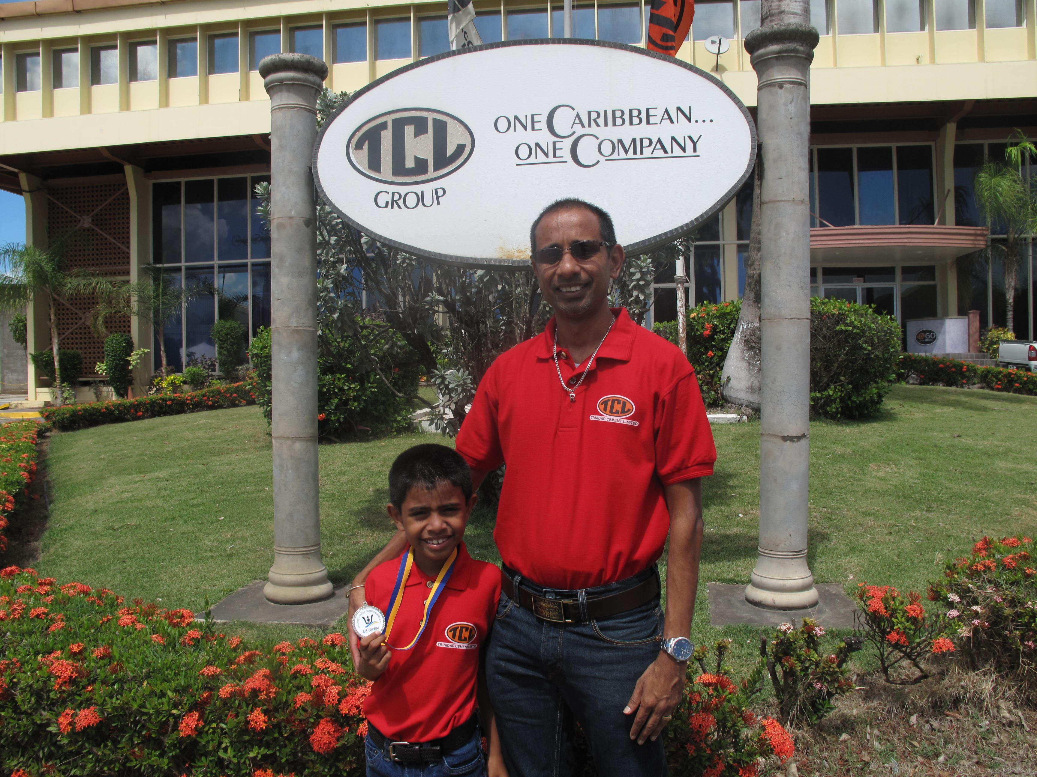 Rayden, displaying his Silver CARIFTA Chess Championship medal, stands in front of TCL's Administration Building with his father, Roydon Rampersad