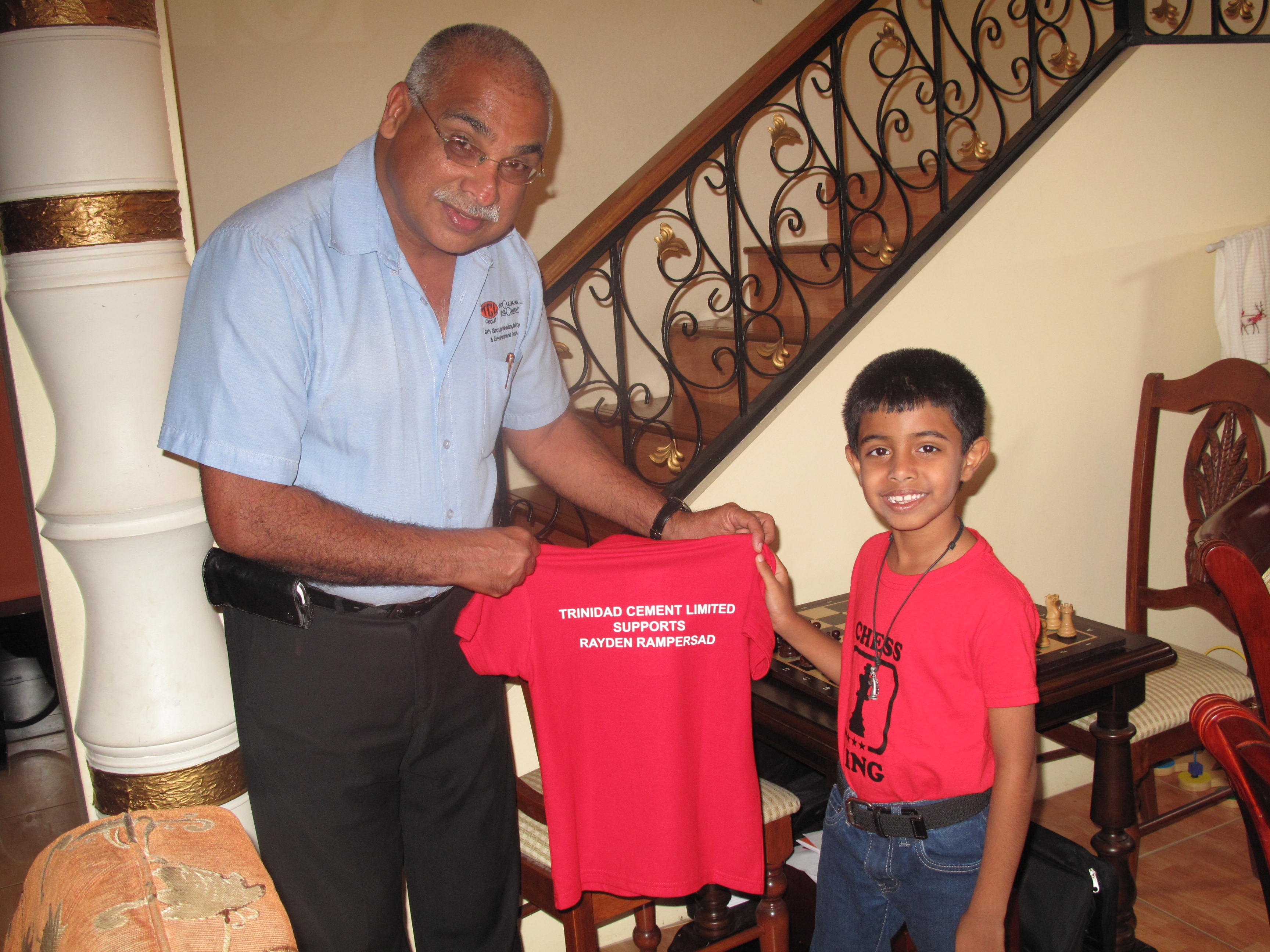 Trinidad Cement Limited's General Manager (Ag.), Jinda Maharaj, with Trinidad and Tobago's Under-8 Chess Champion, Rayden Rampersad.  TCL proudly sponsored Rayden Rampersad's participation in the 2015 CARIFTA Chess Championship.